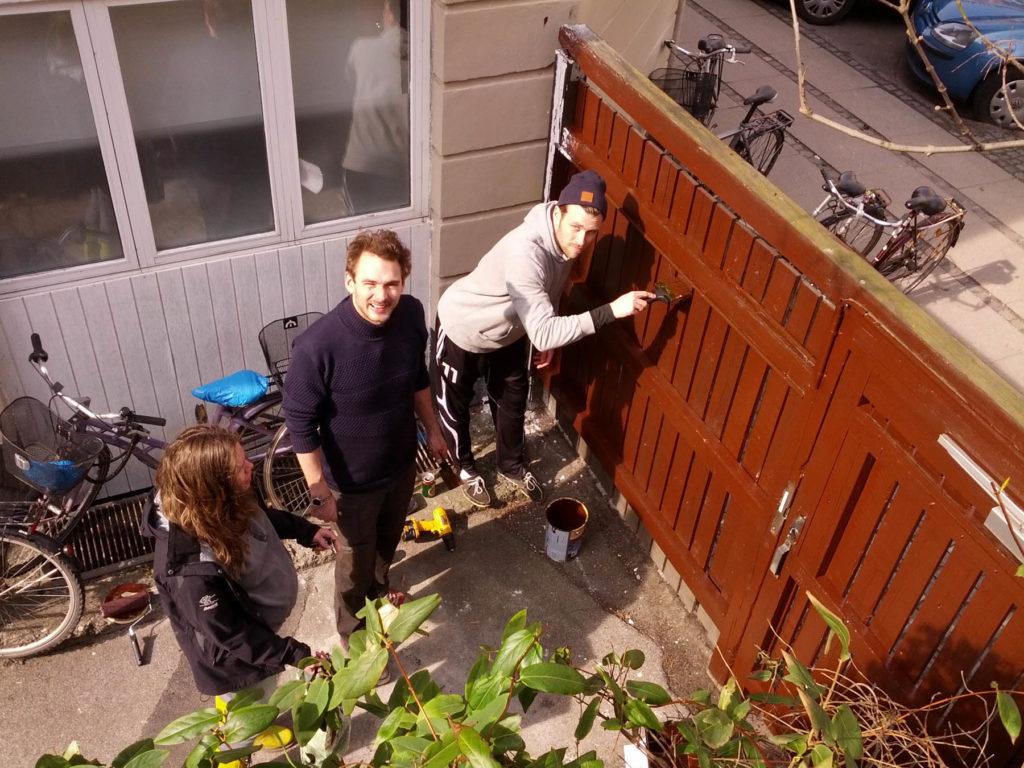 Mads, Jeppe og Sofie maler det sidste af porten