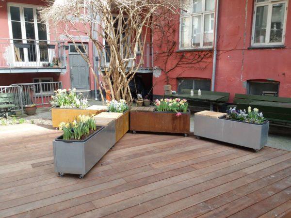 Plantekummmer på trædæk med plantekasser og bænke