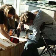 Søren (med skruemaskinen) hjælpes af Anders med at sætte topbrædder på vores nyeste plantemøbel