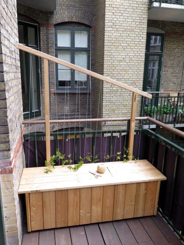 Selvvandende plantekassebænk med slyngplanter og rum til opbevaring i bænken.