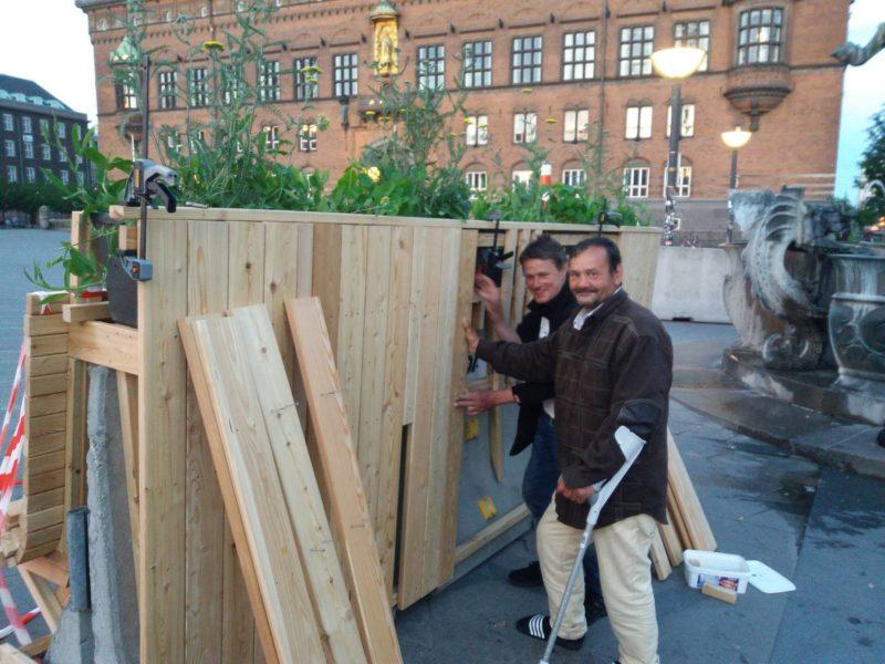 Polle og Richard hjælper med at holde brædder, på den side hvor cykelparkering skal være.