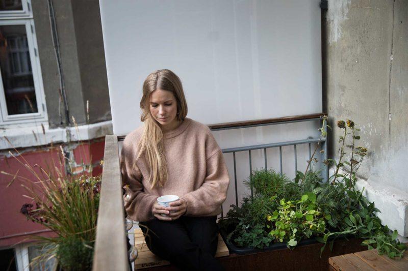 Anna nyder en kop the på sin kombinerede bænk og plantekasse